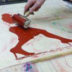 ein Tango- Holzschnitt wird mit roter Farbe eingewalzt