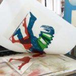Foto: ein Holzschnitt wird gedruckt, die Farbe rot wird gerade abgezogen